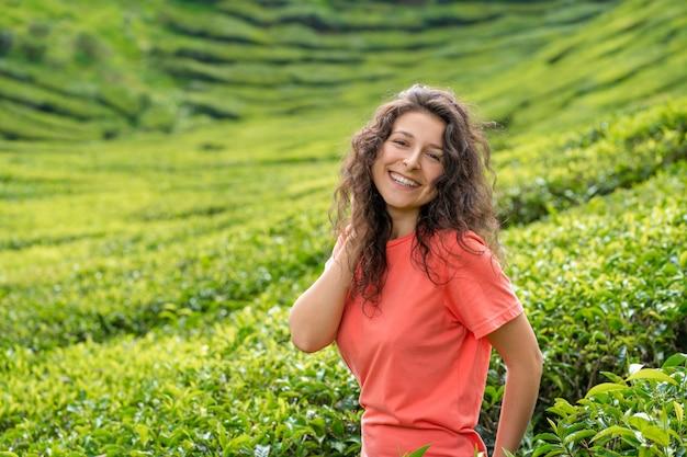 Linda menina morena posando no meio do vale do chá, entre arbustos de chá verde.