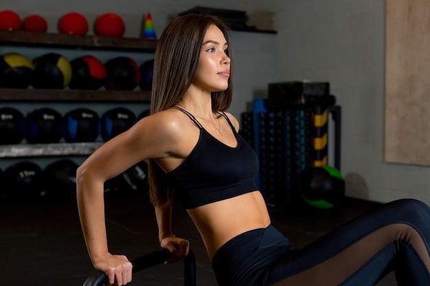 Linda menina morena realiza um exercício para fortalecer os músculos das mãos na academia por um conjunto de bolas.