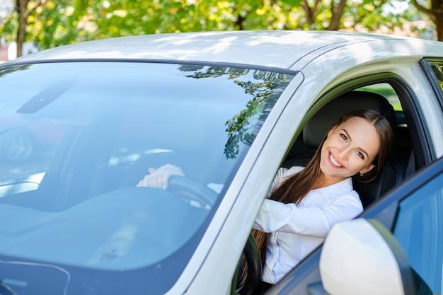 Linda menina morena sorridente ao volante de um carro