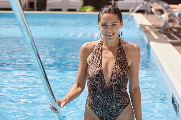 Linda menina morena sorridente, saindo da piscina, vestindo maiô de leopardo, posando com o cabelo molhado