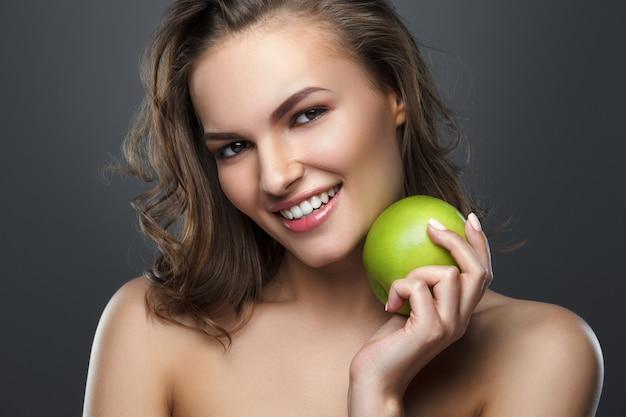 Linda menina morena sorridente segurando uma maçã verde