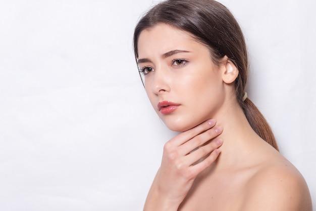 Linda menina morena tem uma dor de garganta isolada no fundo branco. infeliz mulher doente, sofrendo de dolorosa deglutição, forte dor na garganta, segurando a mão no pescoço. conceito de saúde.
