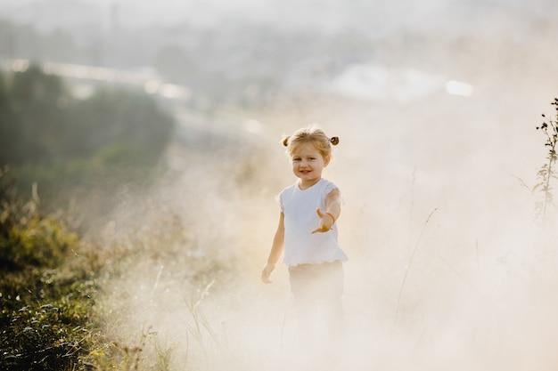 Linda menina na camisa branca e calça jeans corre no gramado no nevoeiro com grande paisagem