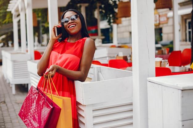 Linda menina negra com sacos de compras em uma cidade