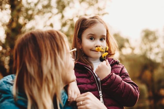 Linda menina olhando para a câmera sorrindo enquanto sorri uma florzinha amarela enquanto sua mãe está olhando para ela ao ar livre.