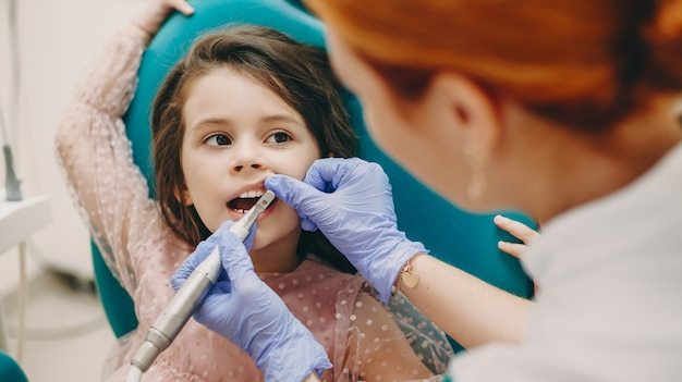 Linda menina olhando para o odontopediatra enquanto faz um exame de dentes em uma estomatologia pediátrica.