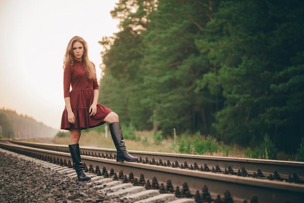 Linda menina pensativa triste com cabelo natural encaracolado na natureza na floresta na estrada de ferro.
