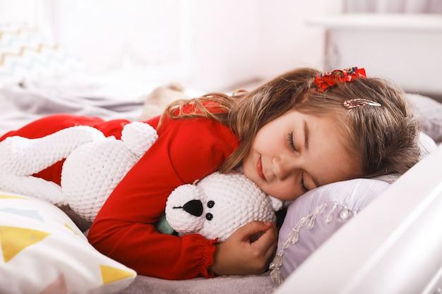 Linda menina pequena está dormindo com um urso branco brinquedo vestido de pijama vermelho