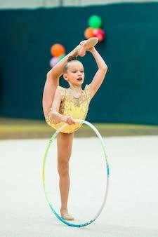 Linda menina pequena ginasta ativa com seu desempenho no tapete