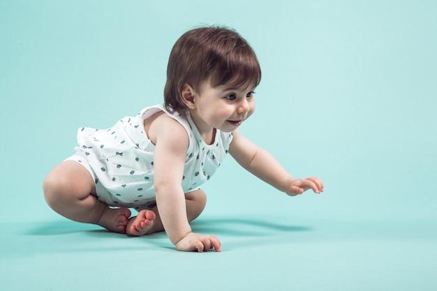 Linda menina pequena rastejando sentado no estúdio, sobre fundo azul