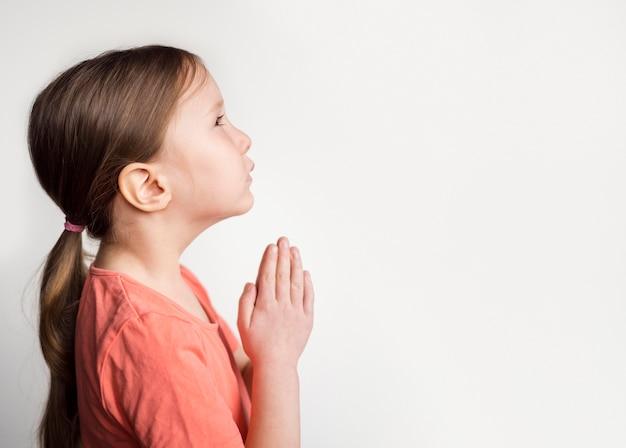Linda menina rezando com espaço de cópia