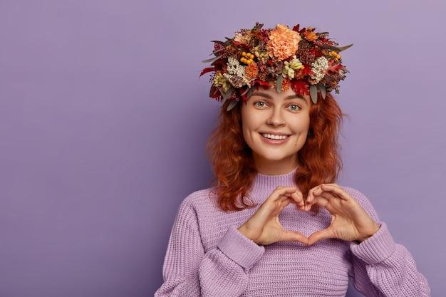 Linda menina ruiva demonstra o sinal do amor, molda o coração com as mãos, tem uma expressão amigável, usa uma linda coroa de outono na cabeça, vestida com um suéter de malha, isolado sobre o fundo roxo