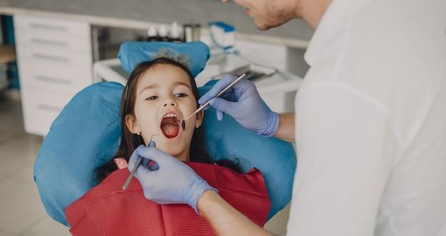 Linda menina sentada em uma cadeira de estomatologia com a boca aberta, enquanto faz um exame de dentes em estomatologia pediátrica.