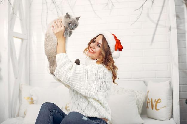 Linda menina sentada em uma cama com gatinho fofo