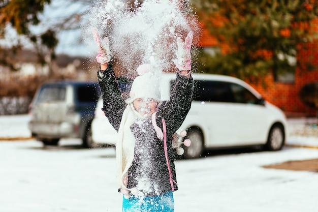 Linda menina sorridente com longos cabelos loiros em rosa de malha chapéu e cachecol e bege casaco em pé no branco