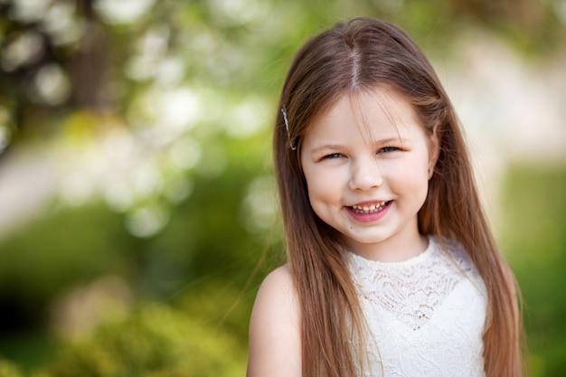 Linda menina sorridente com vestido creme, contra o verde do parque de verão
