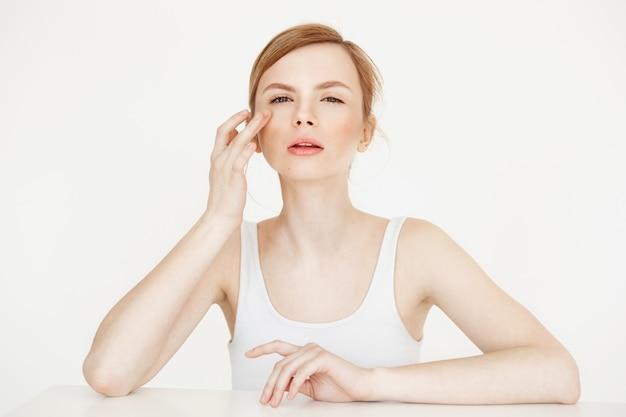 Linda menina tocando a pele, sentado à mesa. cuidados com a pele cosmetologia e beleza.
