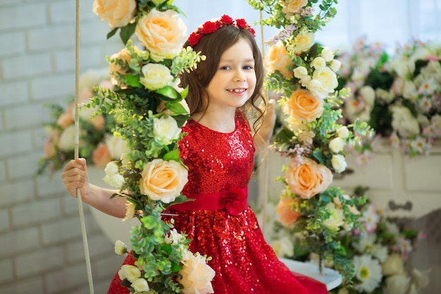 Linda menina vestida de vermelho sentada em um balanço com decoração de flores