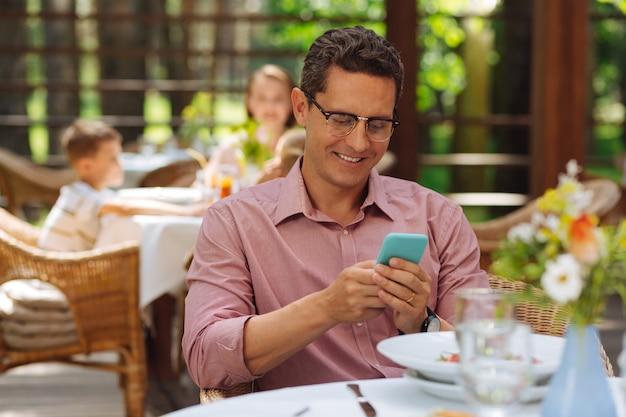 Linda mensagem. homem de cabelos escuros sorrindo abertamente enquanto lê as mensagens de sua linda esposa