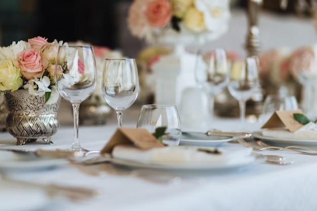 Linda mesa servida com vidro e cerâmica, decorada com flores, preparada para evento festivo.