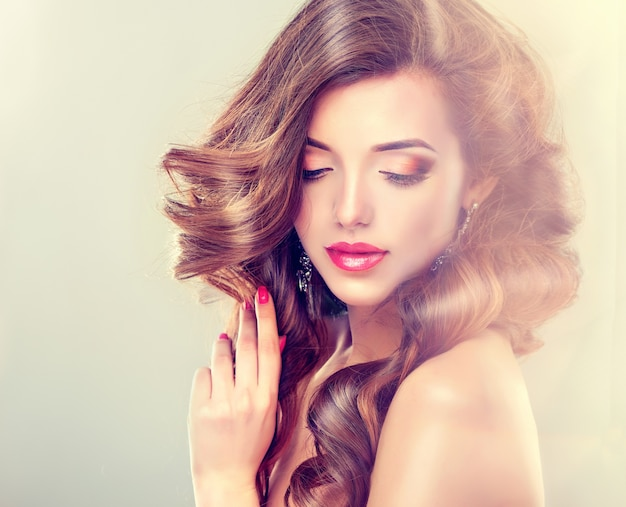 Linda modelo com cabelos longos, densos e cacheados e maquiagem viva com batom vermelho. arte para cabeleireiro, cuidados com os cabelos e produtos de beleza.