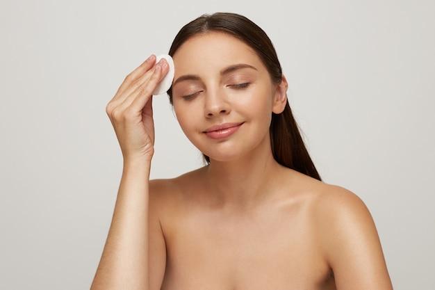 Linda modelo com olhos fechados e ombros nus posando