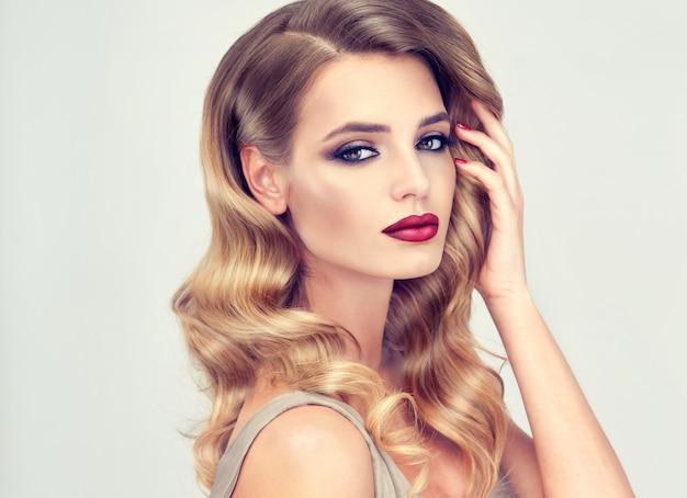 Linda modelo com penteado de noite longo, denso e cacheado e maquiagem vívida com pálpebras esfumadas, pálpebras e batom vermelho. arte para cabeleireiro, cuidados com os cabelos, cosméticos e produtos de beleza.
