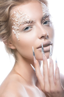 Linda modelo com unhas compridas, maquiagem criativa e design de manicure.