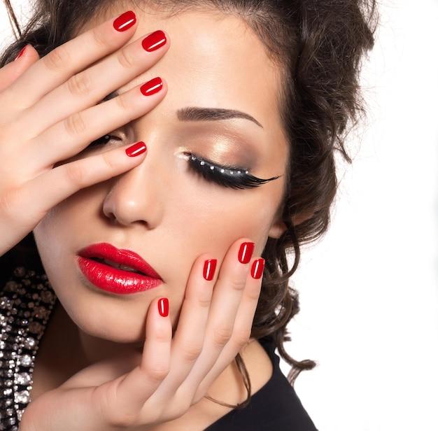 Linda modelo com unhas vermelhas, lábios e maquiagem criativa nos olhos - isolada na parede branca