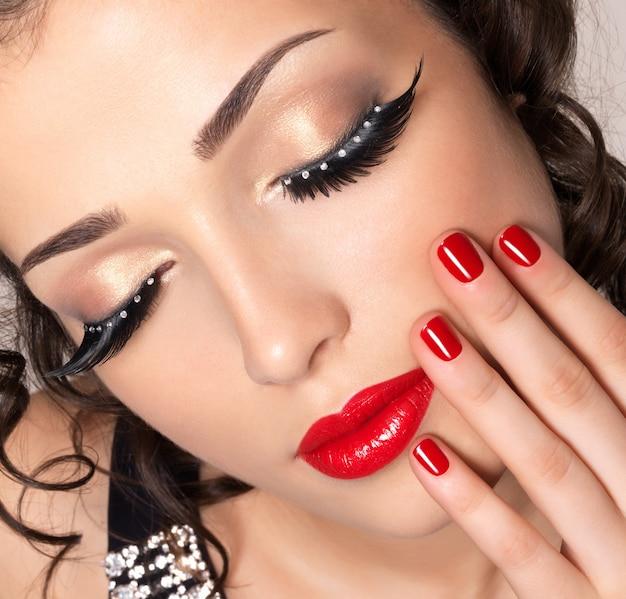 Linda modelo com unhas vermelhas, lábios e maquiagem criativa nos olhos -