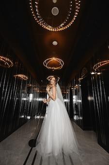 Linda modelo em um vestido de noiva caminhando pelo corredor escuro