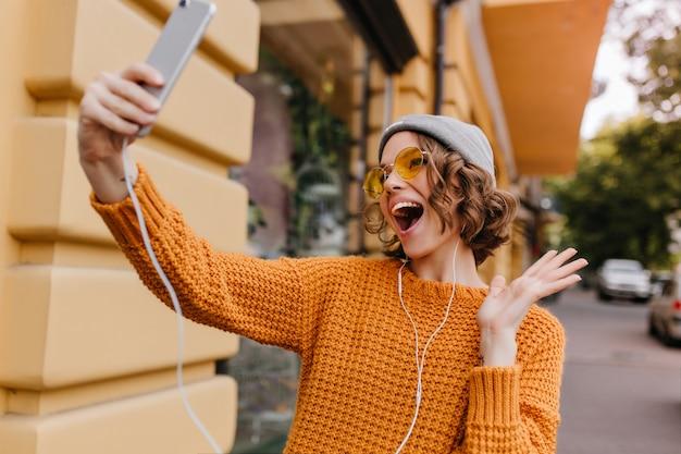 Linda modelo feminina de chapéu cinza, brincando na rua enquanto faz selfie