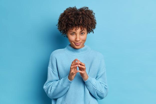 Linda modelo feminina de pele escura olha misteriosamente para a câmera e tem uma expressão complicada enquanto trama algo e dedos agudos fazem planos fica em um estúdio usando um suéter azul casual