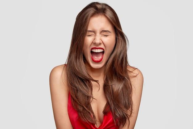Linda modelo feminina exclama com raiva, sendo emotiva, tem lábios vermelhos, pele pura e saudável, mostra ombros nus, isolada sobre parede branca. pessoas, estilo, maquiagem, conceito de emoções