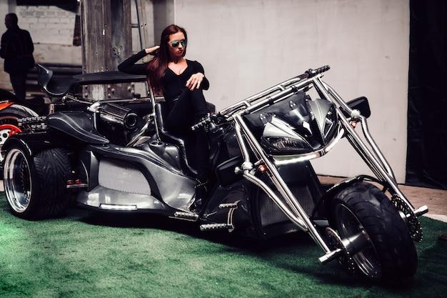 Linda modelo feminina posando sentada em uma motocicleta legal