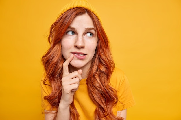 Linda modelo feminina ruiva de olhos azuis mantém o dedo perto dos lábios e tenta se decidir, focada no certo, contempla sobre algo que usa chapéu