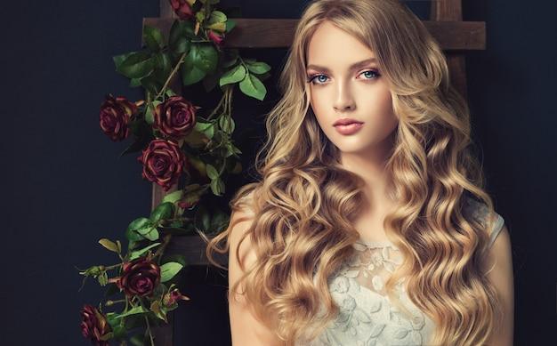 Linda modelo jovem, loira, com cabelos longos, ondulados, bem tratados e crespos. penteado elegante e solto com cachos soltos. arte de cabeleireiro, cuidados com os cabelos e maquiagem.