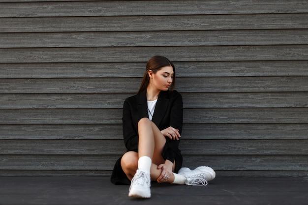 Linda modelo mulher com um casaco preto elegante e tênis branco sentada perto de uma parede de madeira