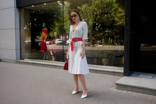 Linda modelo parece mulher morena com vestido branco com bolinhas pretas enquanto acorda na superfície de uma rua da cidade com bolsas elegantes na mão