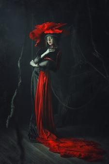 Linda modelo rosa chapéu está posando em um escuro