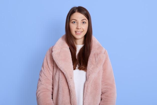 Linda modelo usando um casaco de pele rosa claro