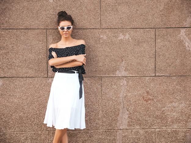 Linda modelo vestida com roupas de verão elegante. garota despreocupada sexy posando na rua perto da parede. empresária moderna na moda em óculos de sol se divertindo