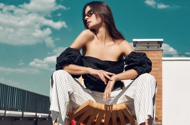 Linda morena brilhante vestido moda, sentado em uma cadeira de madeira