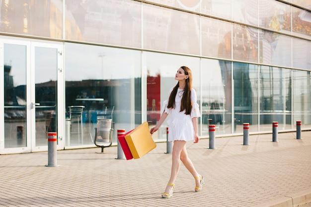 Linda morena com cabelos longos, andando com sacolas de compras antes de um moderno edifício de vidro