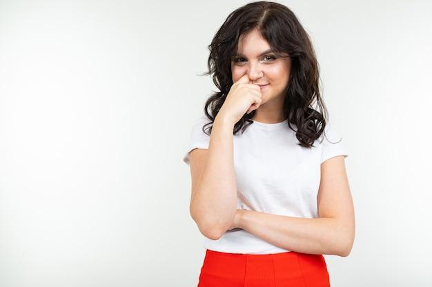 Linda morena com camiseta branca e calça vermelha, isolado no fundo branco.