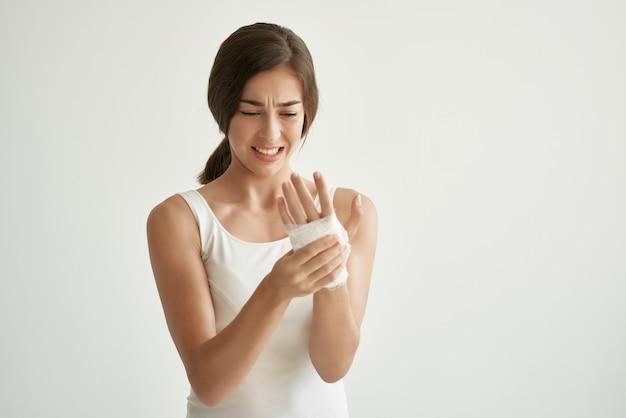Linda morena em t-shirt branca descontentamento por lesão no braço. foto de alta qualidade