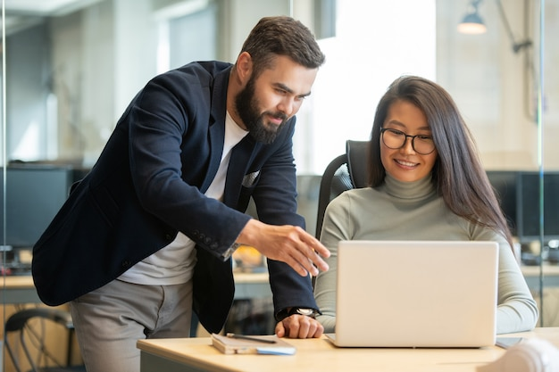 Linda morena empresária asiática olhando para a tela do laptop enquanto seu colega feliz aponta para ela e a ajuda com a apresentação