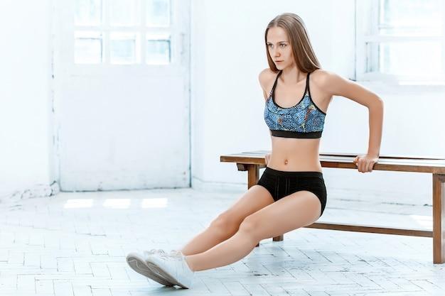 Linda morena esguia fazendo flexões na academia