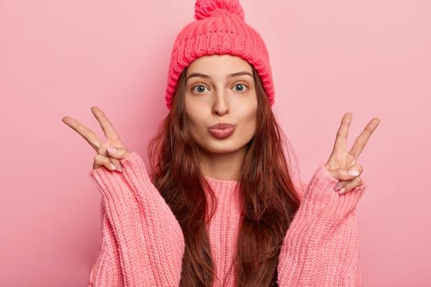 Linda morena europeia jovem mantém os lábios arredondados, faz gesto de paz de vitória, usa chapéu de malha e suéter grande, tem cabelo comprido, isolado sobre fundo rosa.
