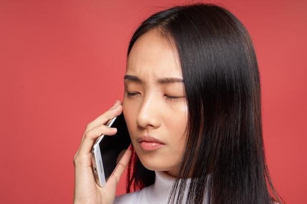 Linda morena falando sobre o fundo de tecnologia vermelho close-up do telefone.